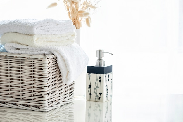White towels in rattan basket on white table with bright room background