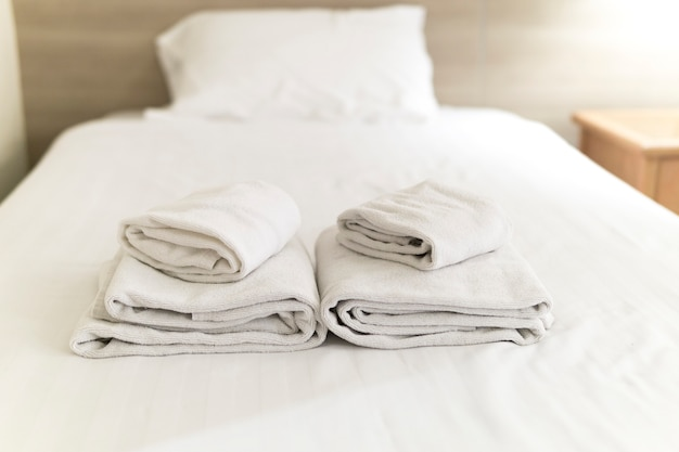 White towels on white bed decoration in bedroom interior hotel.
