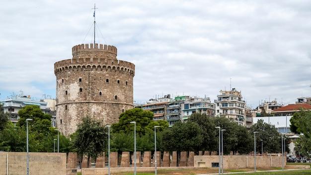 Белая башня в салониках с гуляющими перед ней людьми