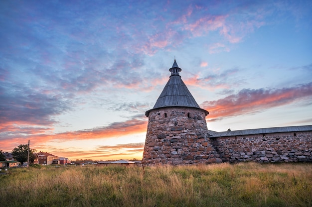 The white tower of the solovetsky monastery against the backdrop of a beautiful sunset autumn sky