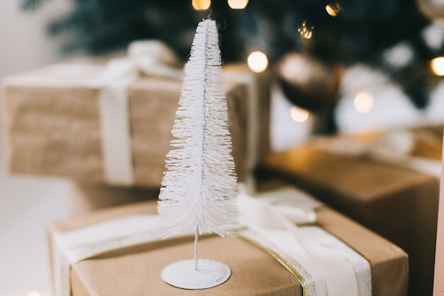クリスマスツリーの下のギフトボックスの隣に白いおもちゃのクリスマスツリー