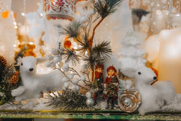 白いおもちゃの子鹿とお祝いの店先の新年に銀色のキラキラとクリスマスツリーの枝