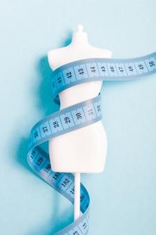 Белый игрушечный манекен, завернутый в синюю измерительную ленту на синей поверхности