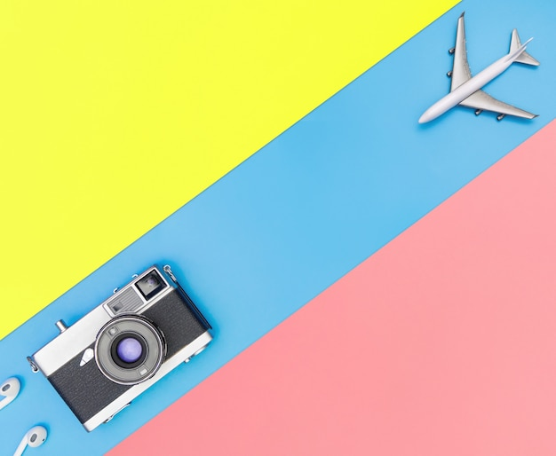 White toy plane and camera on blue and yellow pink background