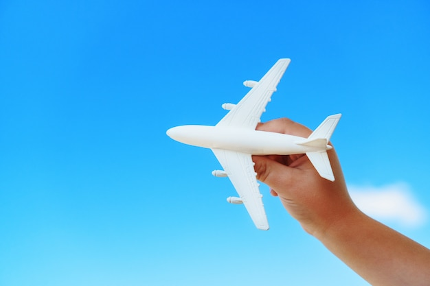 A white toy plane in a child's hand against a blue sky.