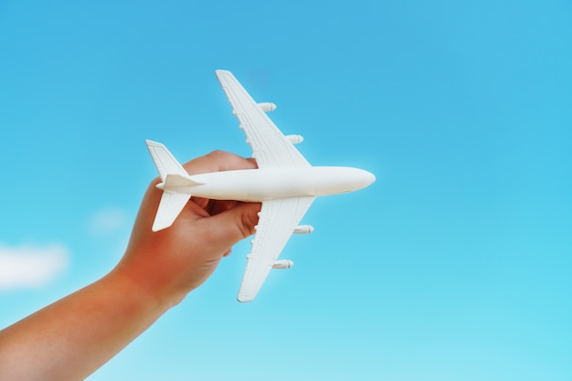 A white toy plane in a child's hand against a blue sky