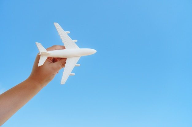 A white toy plane in a child's hand against