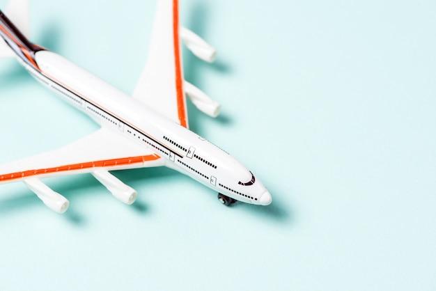 ライトブルーの背景に白いおもちゃの飛行機。上面図
