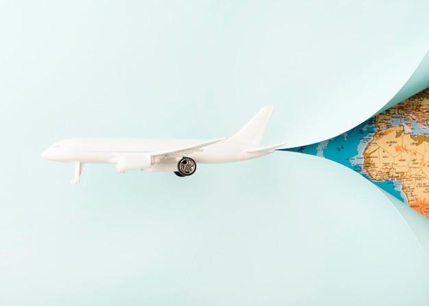 世界地図と白いおもちゃの飛行機