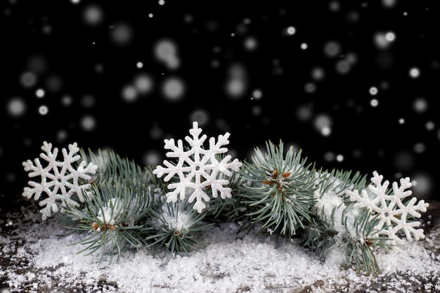 黒い背景の雪の中でクリスマスツリーの枝に白いおもちゃの雪片