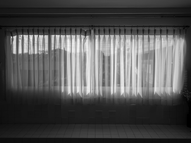 White transparent curtain at the window in the dark room. large horizontal window with closed white fabric curtain.