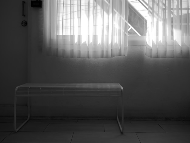 White transparent curtain at the window in the dark room. window with staircase for fire exit at the outside, white fabric curtain and empty white steel bench near the door in the building.