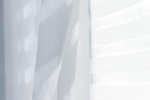 Белый прозрачный занавес с белыми жалюзи на окне.