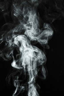 White transparent smoke blowing over black background