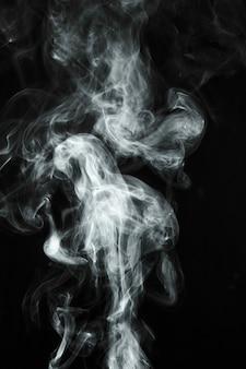 黒い背景に吹く白い透明な煙
