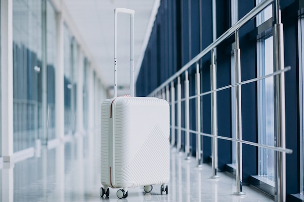 White travel bag isolated alone by the gates