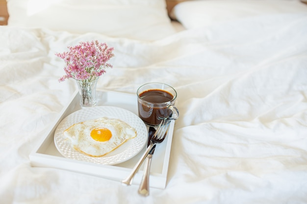 White tray with breakfast on a bed in a hotel room. fried egg, cup of coffee and flowers in white sheets in light bedroom. copyspace.
