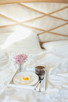 White tray with breakfast on a bed in a hotel room. fried egg, cup of coffee and flowers in white sheets in light bedroom.
