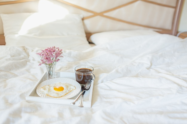 Белый поднос с завтраком на кровати в гостиничном номере. жареные яйца, чашка кофе и цветы в белых листах в светлой спальне. copyspace.