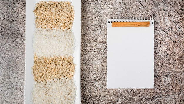 White tray with different type of uncooked rice with spiral notepad and cinnamon against weathered backdrop