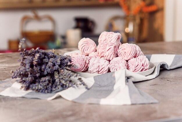 Белый поднос со свежими зефирами на мраморном столе с полотенцем и лавандой.