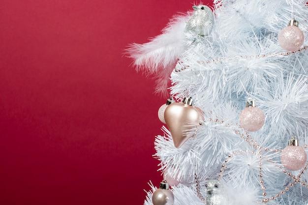Белое дерево украшено декоративными игрушками, шарами, сердечком и декоративной серебряной птицей на бордовом фоне. пустое место для текста. зимний праздник, новый год, рождество. рождественская елка крупным планом.