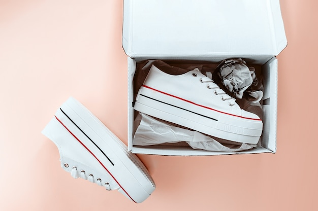 White trendy white sneakers in carton box on creamy peach background