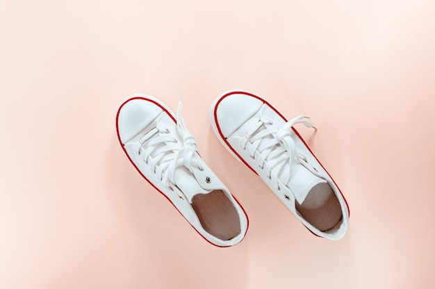 White trendy white sneakers on creamy peach background