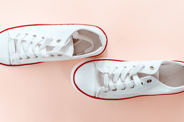 White trendy white sneakers on creamy peach