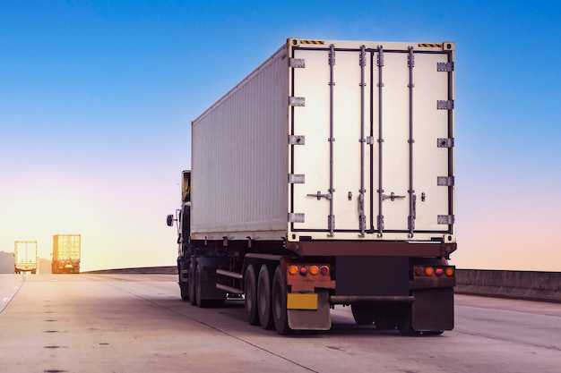 White truck on highway road with  container, transportation concept.import,export logistic industrial transporting land transport on the asphalt expressway against sunrise sky