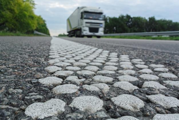 Белый грузовик быстро движется по шоссе летом