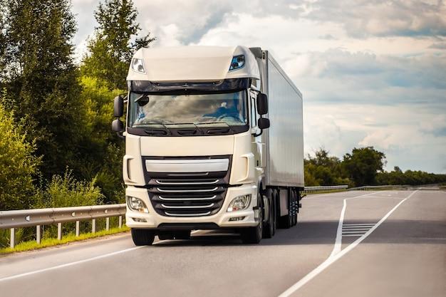 Белый грузовик движется по дороге летом