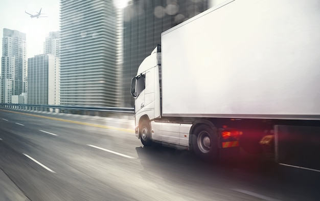 White truck moving fast on the highway with a modern city