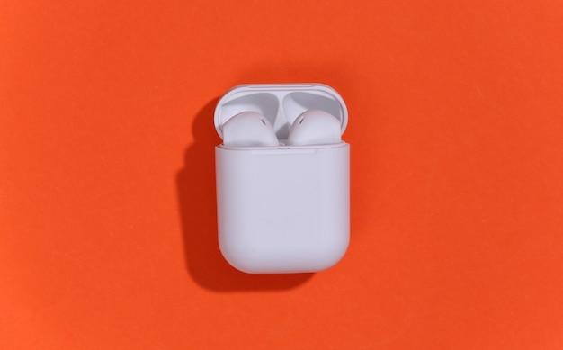 オレンジ色の明るい背景の充電ケースに白い真のワイヤレスbluetoothヘッドフォンまたはイヤフォン。