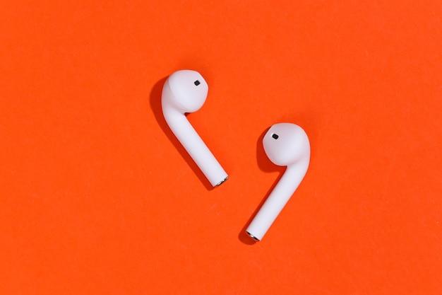 オレンジ色の明るい背景に白い真のワイヤレスbluetoothヘッドフォンまたはイヤフォン。