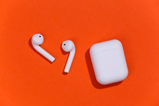 オレンジ色の明るい背景に充電ケース付きの白い真のワイヤレスbluetoothヘッドフォンまたはイヤフォン。