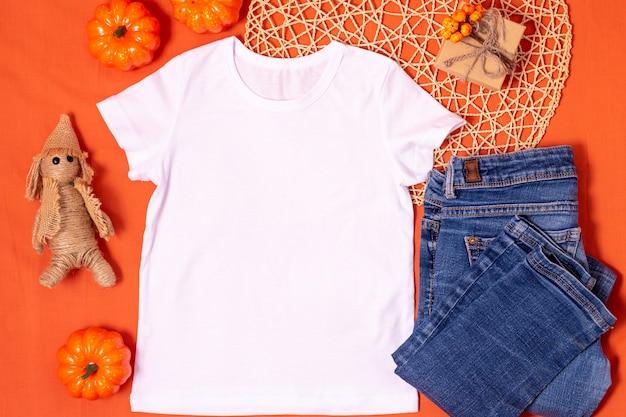 Макет белой футболки на оранжевом фоне хэллоуина