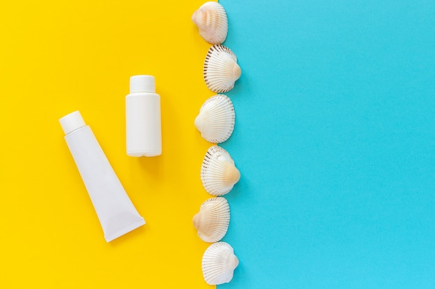 White tube, bottle of sunscreen and line seashells on yellow and blue background, mockup