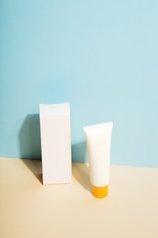 White tube and box of sunscreen on blue background sun protection