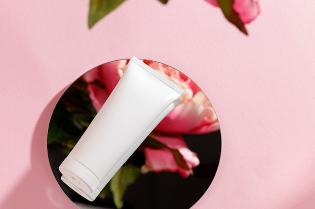 White tube of cream and mirror on pink background