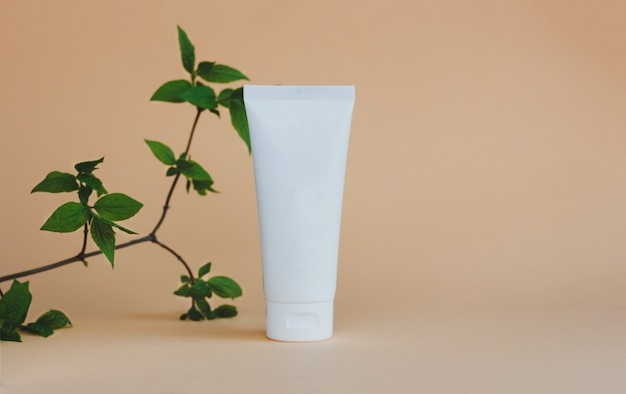 A white tube of cream scrub or lotion stands on a beige background under green leaves natural ecofri...