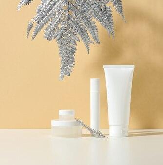 화장품용 흰색 튜브, 흰색 테이블에 크림과 은박이 한 병. 베이지색 그림자 배경에 화장품입니다. 크림병, 로션, 클렌저, 스킨케어용 샴푸