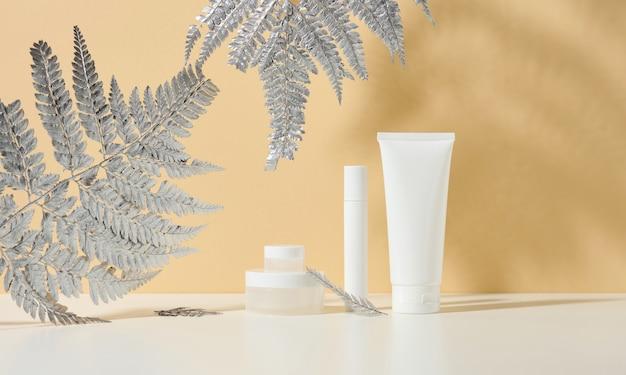 화장품용 흰색 튜브, 흰색 테이블에 크림과 은색 항아리. 베이지색 그림자 배경에 화장품입니다. 크림병, 로션, 클렌저, 스킨케어용 샴푸