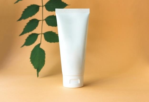Белая тюбик крема с зелеными листьями, концепция натуральной органической спа-косметики