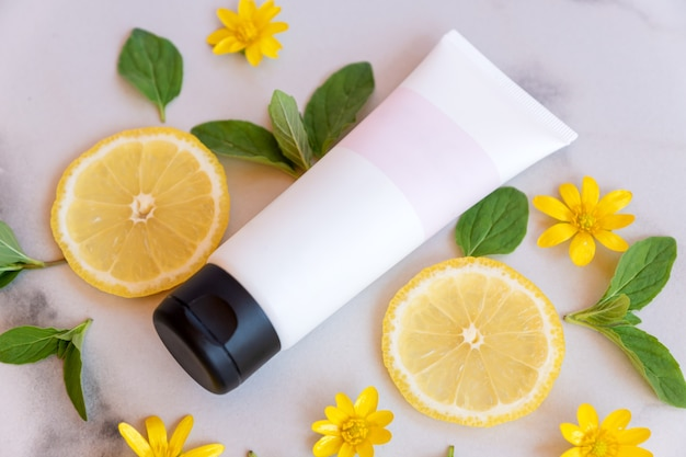 White tube with blank label decorated with fresh lemon slices and green leaves on marbe surface