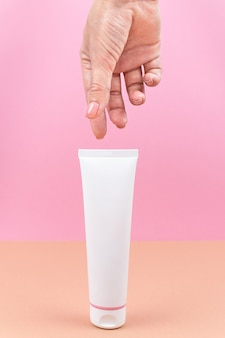 White tube with cream in a womans hand closeup of cosmetic product on pink and orange background