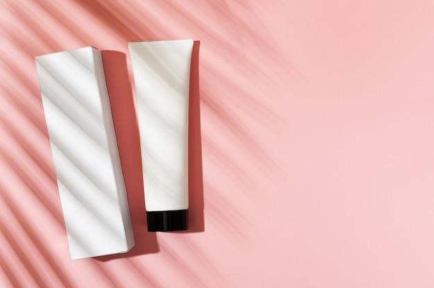 분홍색 배경에 마분지 포장이 있는 거품, 손, 바디 크림이 있는 흰색 튜브. 로벨리니 야자수 그늘로 여성의 여름 케어를 위한 코스메틱 뷰티 제품. spf 자외선 차단 로션.