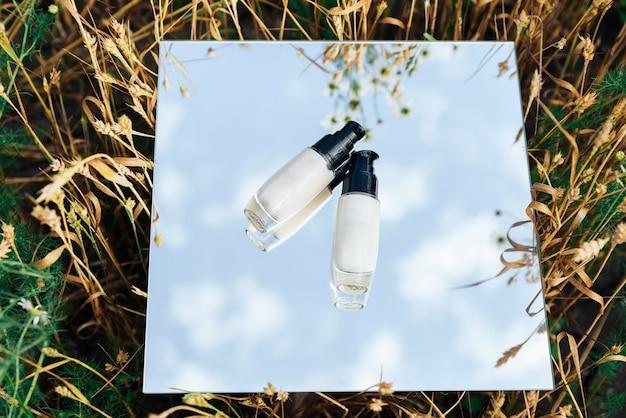 Белые тюбики крема в поле на зеркальной поверхности