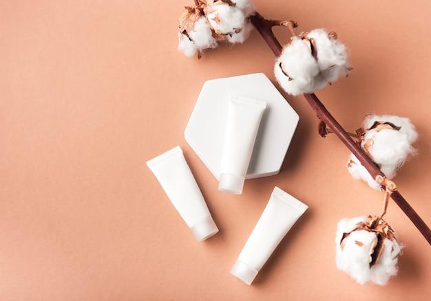 茶色の背景と綿の花の装飾的な枝にクリームの白いチューブ