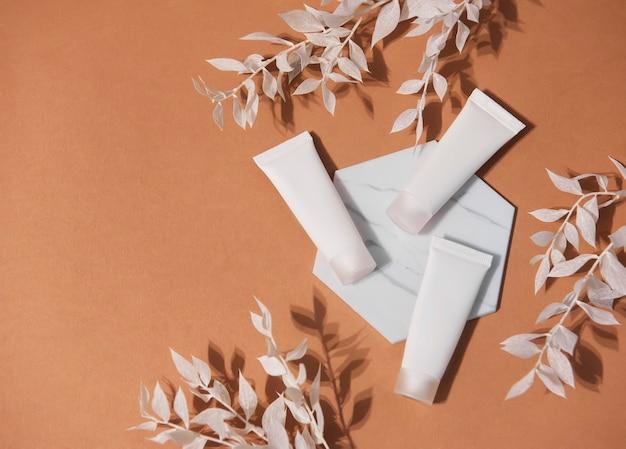 갈색 배경과 흰색 잎 장식 지점에 크림의 흰색 튜브